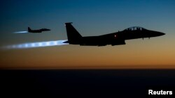 FILE - A pair of U.S. Air Force F-15E Strike Eagles fly over northern Iraq after conducting airstrikes in Syria, in this U.S. Air Force handout photo taken Sept. 23, 2014.