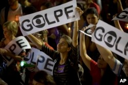 Para demonstran memegang spanduk-spanduk bertuliskan 'Kudeta' dalam Bahasa Portugis, dalam protes pro-pemerintahan di Rio de Janeiro, Brazil (10/5).