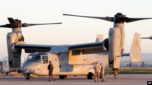 US Marine  officers work next to an MV-22 Osprey vertical take off and lift aircraft , in the Sigonella airbase, Sicily, Thursday, March 24, 2011
