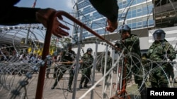 Thai soldiers set up a barbed-wire fence at the Government's temporary headquarters as farmer protesters gather outside in Bangkok on February 10, 2014.