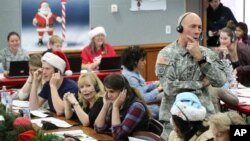 FILE - NORAD and U.S. Northern Command Chief of Staff Maj. Gen. Charles Luckey joins other volunteers taking phone calls from children around the world asking where Santa is, at Peterson Air Force Base, Colo., Dec. 24, 2014.