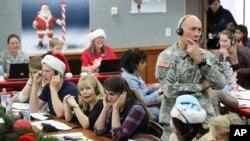 Các nhân viên NORAD và Tham mưu trưởng Bộ Chỉ huy Phòng không Bắc Mỹ, Thiếu tướng Charles Luckey, cùng các tình nguyện viên trả lời điện thoại của trẻ em trên khắp thế giới hỏi về đường đi của ông già Noel tại Căn cứ Không quân Peterson, ở Colorado, ngày 24/12/2014.