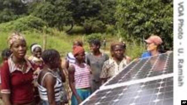 Des villageois dans le District de Kalale scrutant un panneau solaire nouvellement installé.