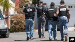 Petugas kepolisian San Diego mendekati rumah yang diyakini merupakan tempat tinggal John T. Earnest (19), yang diduga pelaku penembakan di sinagoga Poway, San Diego, California, Sabtu, 27 April 2019. (John Gibbins / The San Diego Union-Tribune via AP)