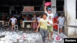 Para penjual dan pembeli berlarian menyelamatkan diri sesaat seusai gempa menghantam wilayah Mandaue di Cebu, Filipina tengah (15/10).Sedikitnya enam orang dilaporkan tewas tertimbun bangunan runtuh di pulau yang populer sebagai daerah tujuan wisata ini.