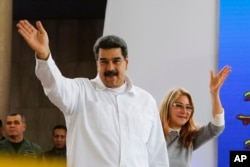 FILE - Venezuela's President Nicolas Maduro, left, and his wife Cilia Flores greet supporters upon their arrival to a meeting with Colombian citizens that reside in Venezuela, in Caracas, Sept. 25, 2018.
