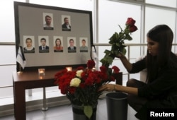 A woman places flowers in front of the portraits of crew members of the crashed Airbus A321 plane, operated by Russian airline Kogalymavia, in the company's office in Moscow, Russia, Nov. 2, 2015.