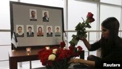 추락한 러시아 여객기 회사 사무실에 사망한 승무원들을 애도하는 초상화가 걸려있는 가운데, 2일 추모객이 초상화 앞에 꽃을 놓고 있다.