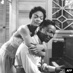"Eartha Kitt hugs Nat King Cole, playing the piano in the role of W.C. Handy, in a scene from the 1958 movie ""St. Louis Blues."""
