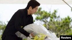 Yaponiya Bosh vaziri Shinzo Abe Okinava orolida urush qurbonlari xotirasi uchun qurilgan yodgorlikka gulchambar qo'ymoqda, 23-iyun, 2015-yil.