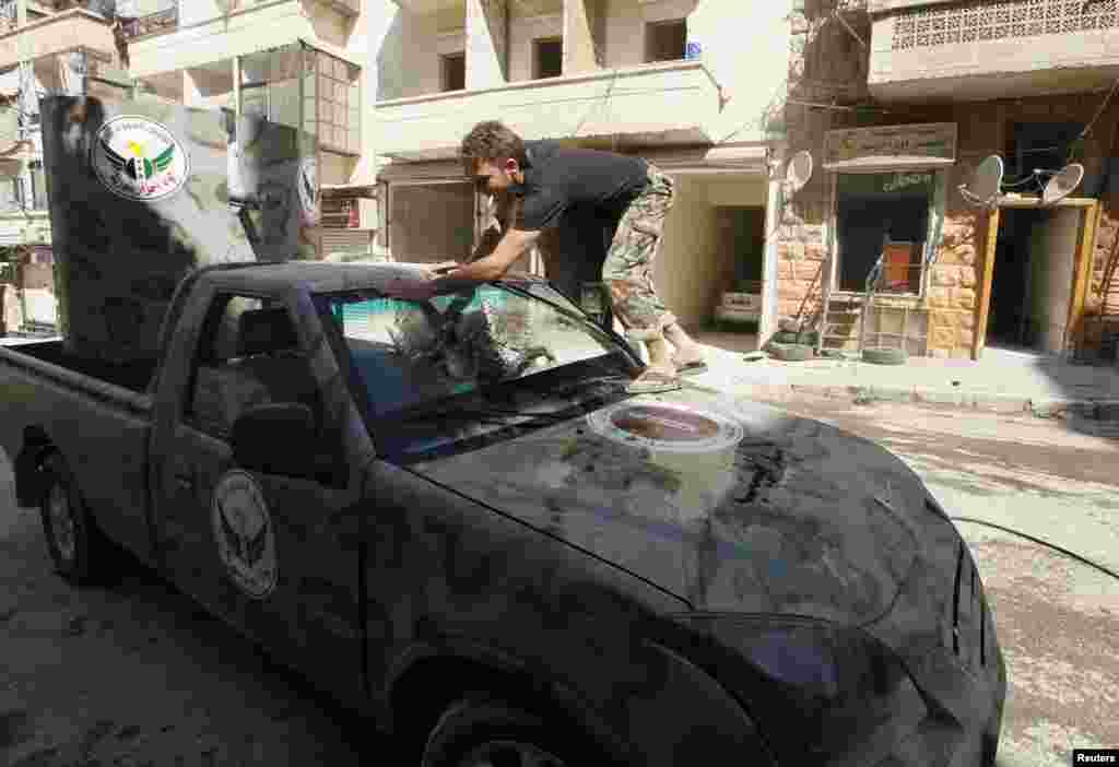 "A member of ""Free Men of Syria"" brigade, operating under the Free Syrian Army, washes a vehicle in Aleppo's Bustan al-Qasr, Sept. 9, 2013."