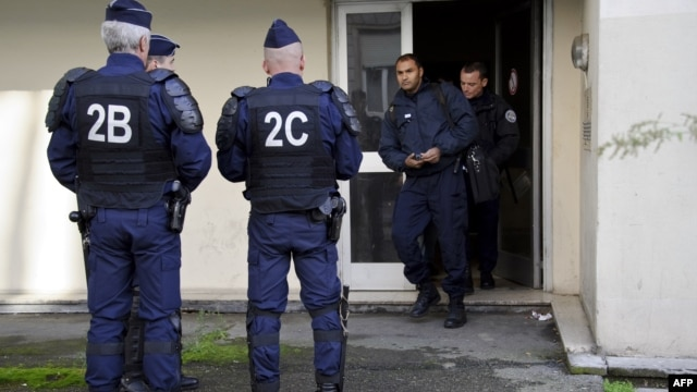 Anti-riot policemen stand outisde an appartment building, where suspects are being arrested by the police during an operation to dismantle a drug trafficking and clandestine immigration network in Mulhouse, eastern France, October 16, 2012.