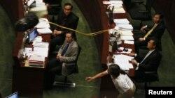 香港立法會議員梁國雄7月16日在立法會向新任特首梁振英投擲面具表示抗議。(路透社)
