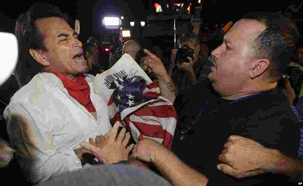 Anti-Castro protester Sisay Barcia (right), argues with pro-Obama supporter Peter Bell in the Little Havana area of Miami, Dec. 17, 2014.