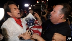 Anti-Castro protester Sisay Barcia, right, argues with pro-Obama supporter Peter Bell, left, in the Little Havana area of Miami, Wednesday, Dec. 17, 2014. (AP Photo/Alan Diaz)