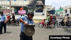"""Một nhà máy ở Bình Dương bị đốt. Phía trước là biểu ngữ với hàng chữ 'Chúng tôi yêu Việt Nam. Hãy bảo vệ chén cơm."""""""