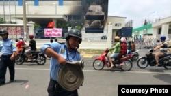 Một nhà máy bị đốt và biểu ngữ căng trước cửa với hàng chữ 'Chúng tôi yêu Việt Nam. Hãy bảo vệ chén cơm'.