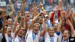 Tim nasional putri AS merayakan kemenangan dengan trofi yang mereka raih setelah mengalahkan Jepang 5-2 dalam kejuaraan sepak bola Piala Dunia Putri FIFA di Vancouver, Kanada (5/7). (AP/Elaine Thompson)