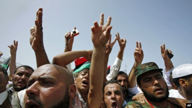 People flash victory signs as they gather at Martyrs Square after Friday prayers in Tripoli, September 2, 2011
