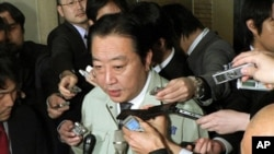 Japanese Finance Minister Yoshihiko Noda (C) speaks to reporters announcing that finance ministers from the G7 group of top economies and central bankers will hold teleconference talks, at his office in Tokyo on March 17, 2011.