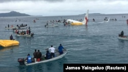 People are evacuated from an Air Niugini plane that crashed in the waters in Weno, Chuuk, Micronesia, Sept. 28, 2018 in this picture obtained from social media.