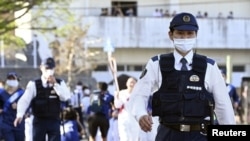 Police officers walk to guard during the Tokyo 2020 Olympic torch relay amid the coronavirus disease (COVID-19) outbreak in Seiyo, Ehime Prefecture, Japan, April 22, 2021. Mandatory credit Kyodo/via REUTERS ATTENTION EDITORS - THIS IMAGE HAS BEEN SUPPLI