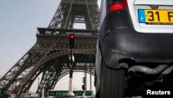 Sebuah mobil melintas dekat Menara Eiffel di Paris (14/3).