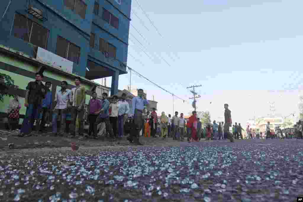 Garment workers walk out from a factory as other workers clash with police in Ashulia on the outskirts of Dhaka, Bangladesh, Nov. 12, 2013.