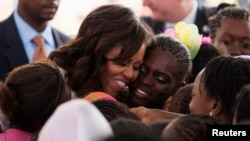 U.S.first lady Michelle Obama hugs students at Martin Luther King middle school, an all-girls school in Dakar, Senegal, June 27 2013.