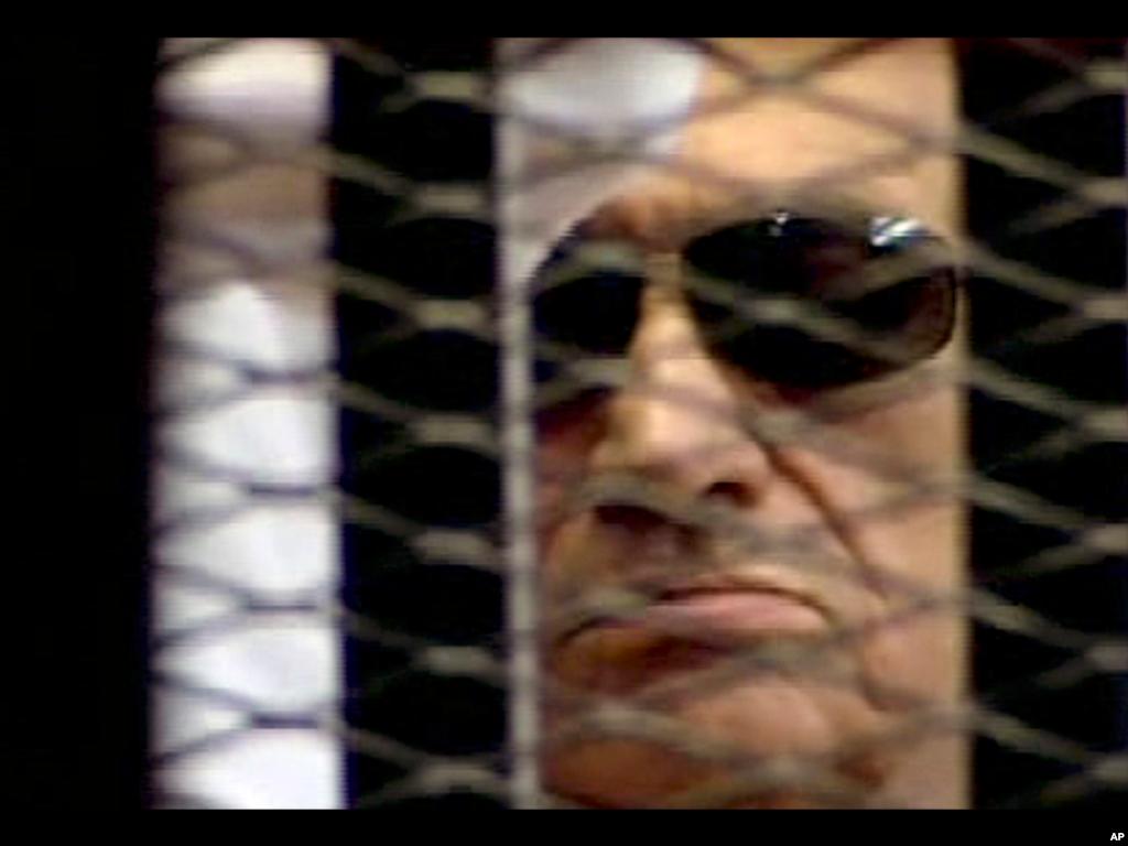 (美联社) 在2012年六月二号埃及国家电视台这段录像的画面中,埃及前总统穆巴拉克在被告囚笼内听取法官宣读对他被控策动杀害抗议民众的定罪