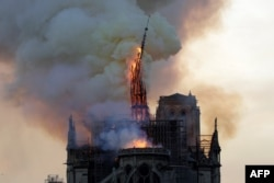 The steeple and spire of the landmark Notre-Dame Cathedral collapses as the cathedral is engulfed in flames in central Paris, April 15, 2019.