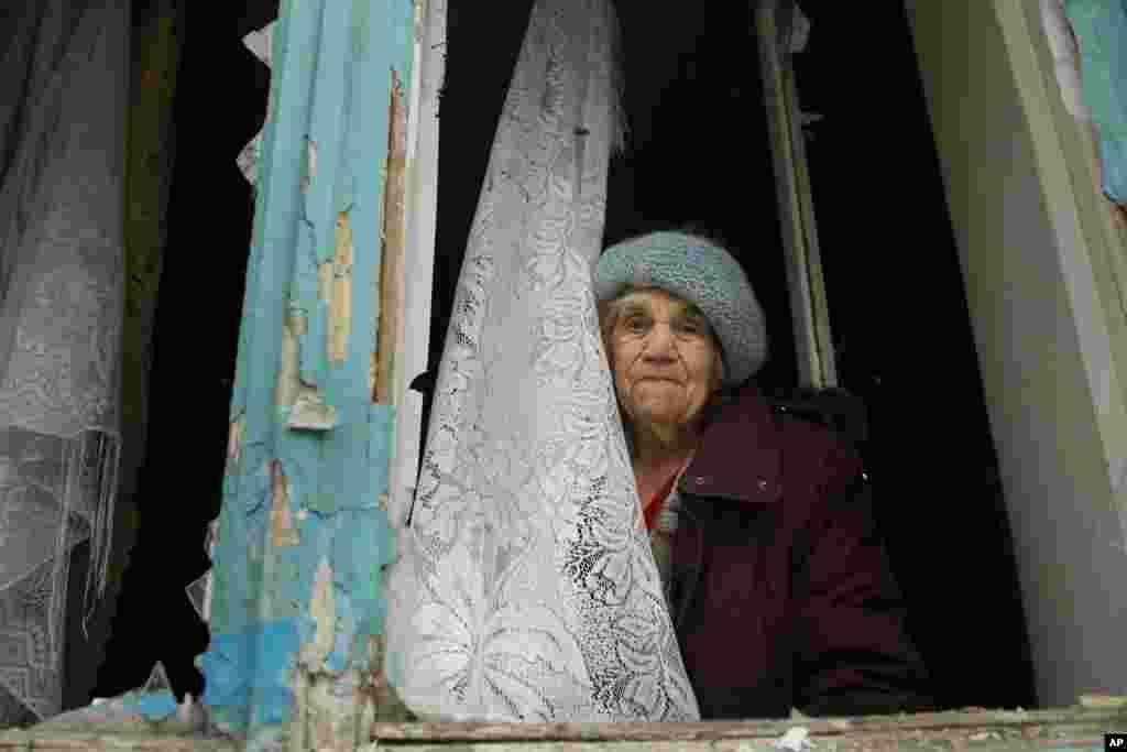 Seorang perempuan lansia tampak sedih setelah apartemen-nya ikut terkena serangan artileri dalam pertempuran di Donetsk, Ukraina timur.