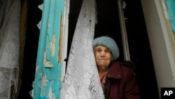 FILE - An elderly woman looks from her damaged flat after artillery shook Donetsk, eastern Ukraine, Feb. 3, 2017.