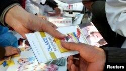 Một người tình nguyện ở Trung Quốc trao tập sách nhỏ chỉ dẫn ngừa HIV/AIDS cùng với condom miễn phí cho người dân trong chiến dịch nâng cao sự hiểu biết về bệnh này ở Bắc Kinh