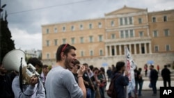 Protesters chant anti austerity slogans in front of the Greek parliament in central Athens, on Friday, May 6, 2016.