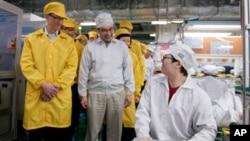 Giám đốc điều hành Apple Tim Cook (trái) thăm dây chuyền sản xuất iPhone tại cơ sở sản xuất Foxconn ở Trung Quốc. Các công ty lớn của Mỹ như Apple sản xuất tại Trung Quốc, nhưng bán sản phẩm tại Hoa Kỳ.
