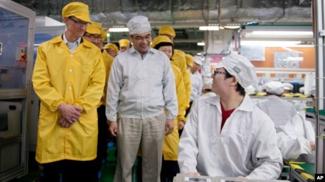 In this March 28, 2012 photo provided by Apple, Inc., Apple CEO Tim Cook, left, visits the iPhone production line at the newly-built manufacturing facility Foxconn Zhengzhou Technology Park, which employs 120,000 people.