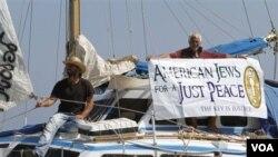 Para aktivis Yahudi di atas kapal bantuan untuk Gaza mengibarkan spanduk sebelum berangkat dari pelabuhan Famagusta, Siprus utara.