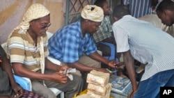 Seorang pelanggan Dahabshiil, sebuah tempat penukaran uang di Somalia, menukarkan lebaran uang dolar dengan mata uang Somalia di Mogadishu, Somalia (Foto: dok).