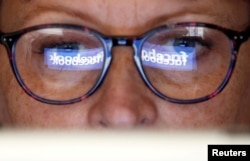 The Facebook logo is reflected on a woman's glasses in this photo illustration taken June 3, 2018