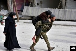 In this photo released by the Syrian official news agency SANA, a Syrian soldier carries a wounded woman in eastern Aleppo, Syria, Dec. 12, 2016.