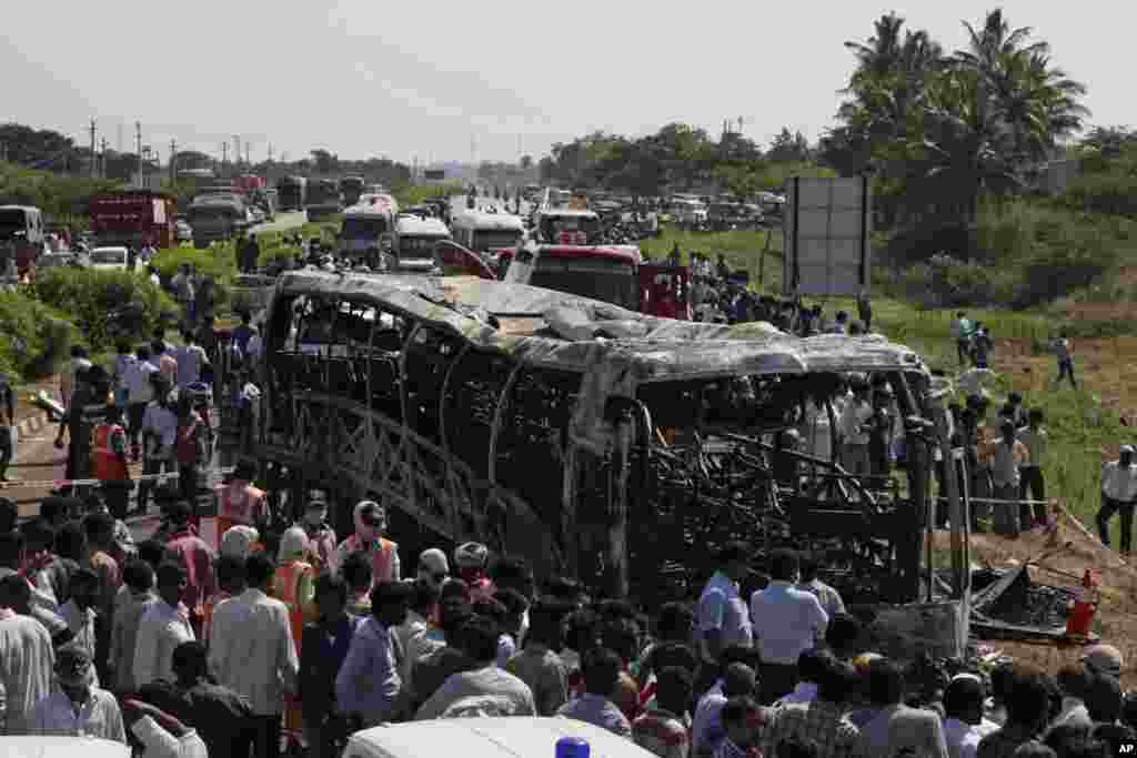 Rescuers and others gather after a bus crashed into a highway barrier and erupted in flames, Mehabubnagar, Andhra Pradesh, India, Oct. 30, 2013.