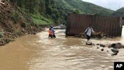Warga berjalan melewati banjir yang menggenangi provinsi utara Son La, Vietnam, Kamis, 12 Oktober 2017.
