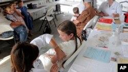 Seorang anak divaksinasi MMR di sebuah klinik Shiloh, Ohio, sementara anak-anak lain menunggu giliran. (Foto: Dok)