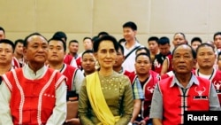 FILE - Myanmar's Foreign Minister Aung San Suu Kyi sits with members of the United Wa State Army (UWSA) following a meeting of armed ethnic groups in Naypyitaw, Myanmar, July 29, 2016.