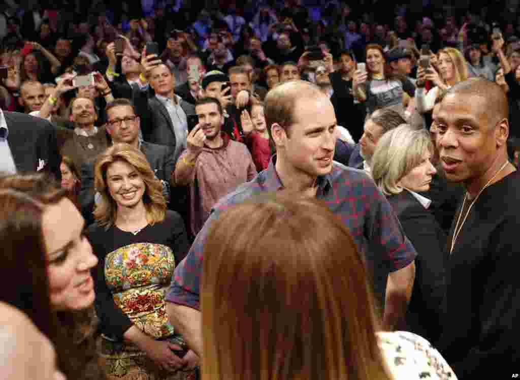 Britain's Prince William, second from right, talks with rapper and entrepreneur Jay-Z, far right, as Kate, left, the Duchess of Cambridge, chats with Jay Z's wife, entertainer Beyonce, foreground center, in New York, Dec. 8, 2014.