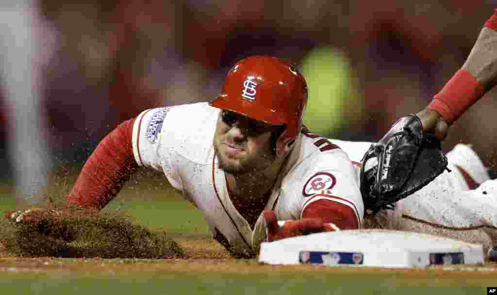 St. Louis Cardinals' Matt Holliday is tagged out at first base during the third inning of Game 3 of baseball's World Series against the Boston Red Sox, Oct. 26, 2013, in St. Louis.
