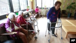 FILE - Kim Gun-ja, 89, right, former comfort woman who was forced to serve for the Japanese troops as a sexual slave during World War II, passes by other comfort woman Yi Ok-seon, 88, left, and Kim Wei-han, 86, at the House of Sharing, a nursing home.