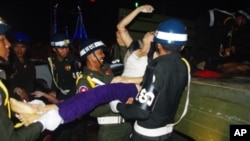 "A female victim of the deadly stampede, on Monday November 22, 2010, is carried onto a rescue truck, by Phnom Penh police. Hou Chanthy, 47, lost her daughter, said, ""I'm thankful for the donations, but the donations will never compensate me."""
