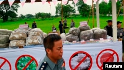 FILE - Police officers are seen near seized drugs which will be burnt, at an event to mark International Day against Drug Abuse and Illicit Trafficking outside Rangoon.